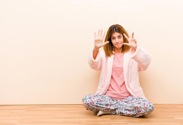 Młoda kobieta w piżamie siedzi w domu uśmiechnięty i przyjazny, pokazuje numer dziewięć lub dziewiąty z ręką do przodu, odliczanie w dół