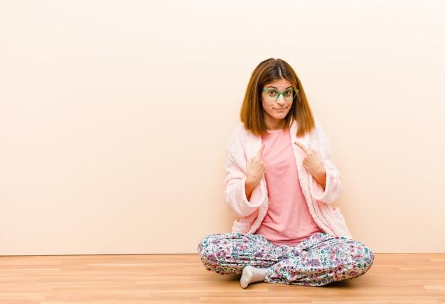 Młoda kobieta w piżamie siedzi w domu, wskazując na siebie z zmieszanym i pytającym spojrzeniem, zszokowana i zaskoczona wyborem