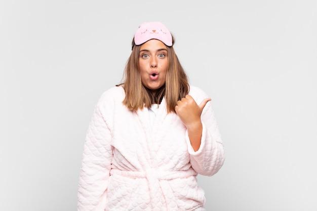 Młoda kobieta w piżamie, wyglądająca na zaskoczoną z niedowierzaniem, wskazująca na obiekt z boku i mówiąca wow, niewiarygodne