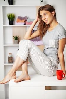 Młoda kobieta w piżamie z pięknym uśmiechem w szatni