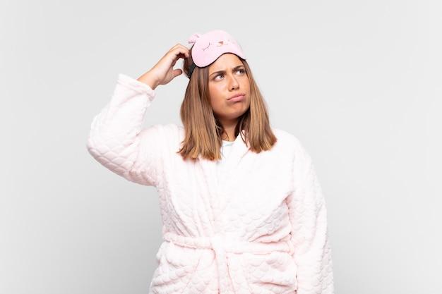 Młoda kobieta w piżamie, zdziwiona i zdezorientowana, drapiąca się po głowie i spoglądająca w bok