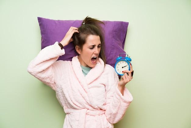 Młoda kobieta w piżamy mienia rocznika zegarze