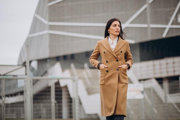 Młoda kobieta w płaszcz stojący na zewnątrz