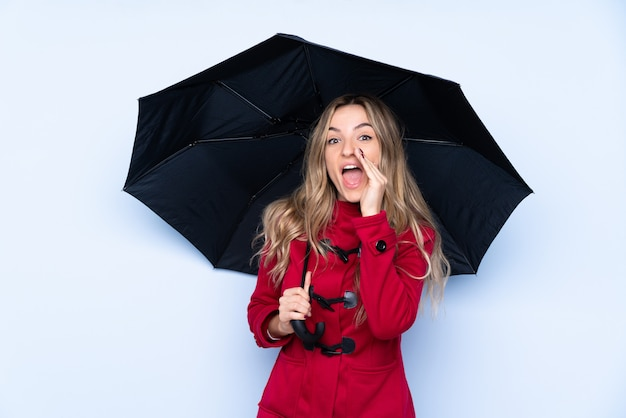 Młoda kobieta w płaszcz zimowy i trzymając parasol krzycząc z szeroko otwartymi ustami