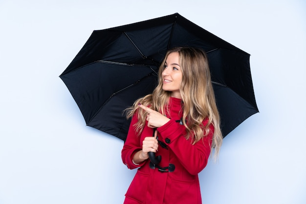 Młoda kobieta w płaszczu zimowym i trzymając parasol wskazujący na bok, aby przedstawić produkt