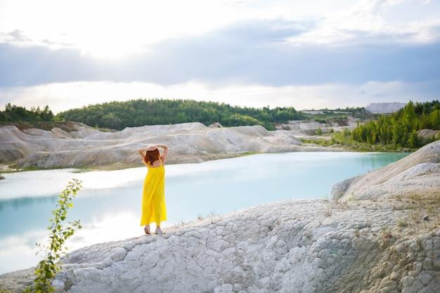 Młoda kobieta w pobliżu jeziora z lazurową wodą i kamienistymi górami z zielonymi drzewami. piękny widok na jezioro w lesie
