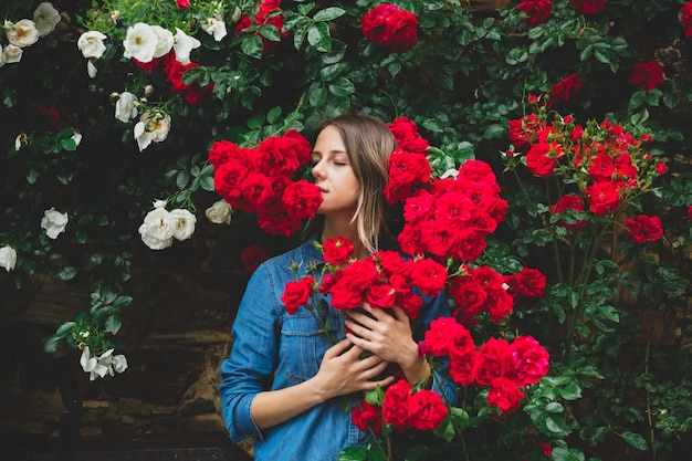 Młoda kobieta w pobliżu krzaka czerwonych róż w ogrodzie