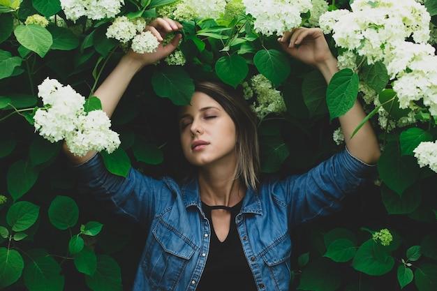 Młoda kobieta w pobliżu krzewu białych kwiatów w ogrodzie