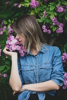 Młoda kobieta w pobliżu krzewu fioletowych kwiatów w ogrodzie