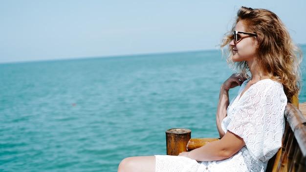 Młoda kobieta w pobliżu morza w białej sukni i okularach przeciwsłonecznych na lazurowym tle