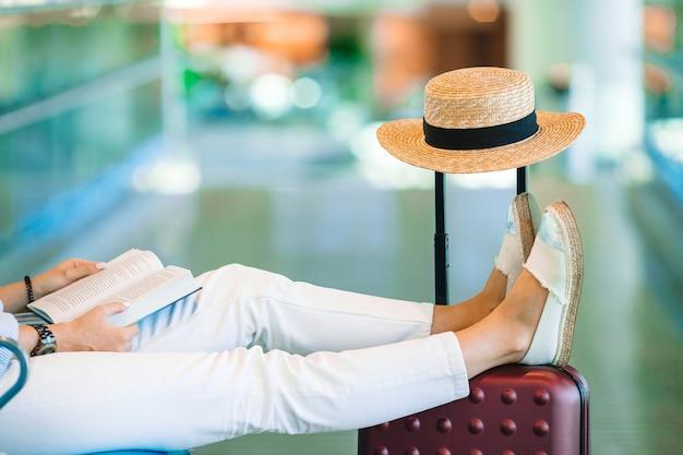 Młoda kobieta w poczekalni na lotnisku czeka na lądowanie. zbliżenie nogi na bagażu