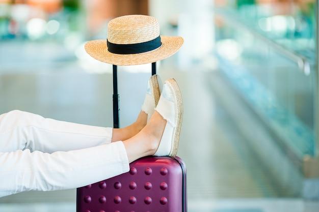 Młoda kobieta w poczekalni na lotnisku czeka na lądowanie.