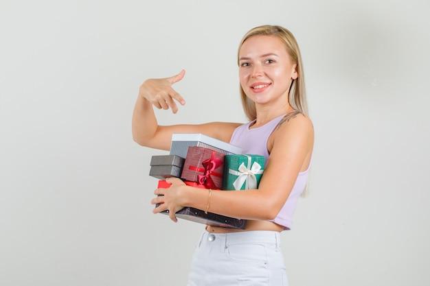 Młoda kobieta w podkoszulek, mini spódniczka, wskazując palcem na pudełka na prezenty i patrząc wesoło
