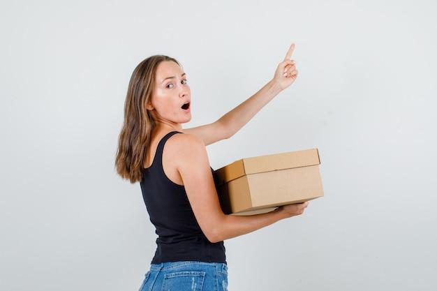 Młoda kobieta w podkoszulek, spodenki, trzymając karton z palcem w górę.