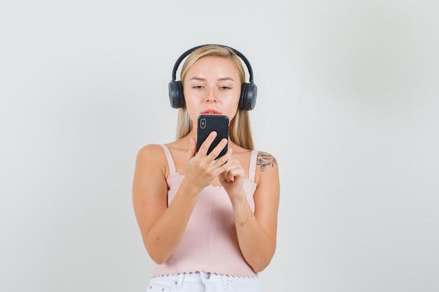 Młoda kobieta w podkoszulku, mini spódniczce, słuchawkach rozmawia przez wideokonferencję