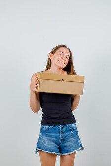 Młoda kobieta w podkoszulku, spodenkach trzyma karton i wygląda na szczęśliwą
