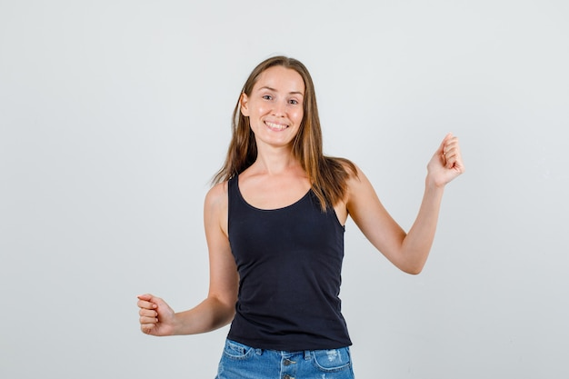 Młoda kobieta w podkoszulku, szortach świętująca zwycięstwo z zaciśniętymi pięściami i wyglądająca na szczęśliwą