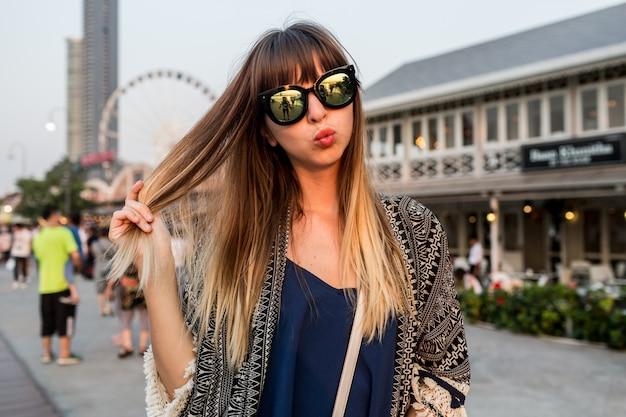 Młoda kobieta w podróży przesyła buziaka, świetnie się bawiąc nad brzegiem bangkoku
