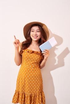 Młoda kobieta w pomarańczowej sukience w kropki i słomkowym kapeluszu na głowie trzyma paszport i bilety lotnicze