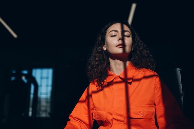 Młoda kobieta w pomarańczowym garniturze kobieta w pomarańczowych kombinezonach w więzieniu