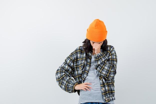 Młoda kobieta w pomarańczowym kapeluszu i kraciastej koszuli pochyla głowę na rękę i wygląda na zdenerwowaną