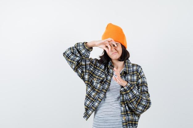 Młoda kobieta w pomarańczowym kapeluszu i kraciastej koszuli udaje, że coś trzyma