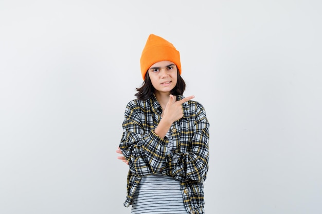 Młoda kobieta w pomarańczowym kapeluszu w kraciastą koszulę, wskazującą na bok, wyglądająca niepewnie
