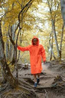 Młoda kobieta w pomarańczowym płaszczu, piesze wycieczki w zielonym lesie. aktywny styl życia i podróże