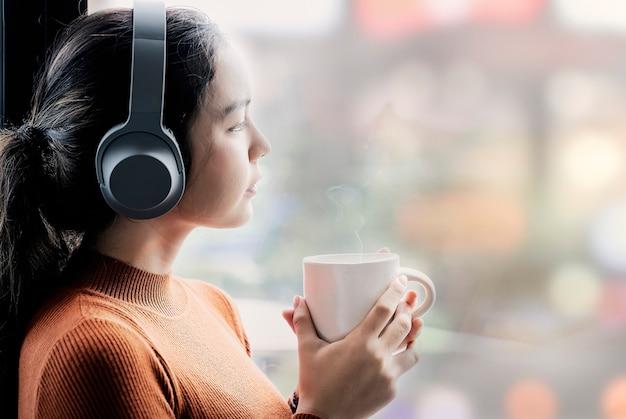Młoda kobieta w pomarańczowym pulowerze słucha musice i trzyma filiżankę podczas gdy stojący okno.