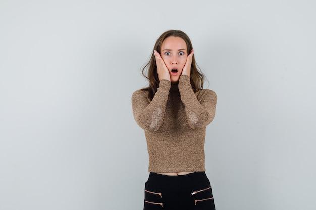 Młoda kobieta w pozłacanym swetrze i czarnych spodniach trzyma ręce na policzkach i wygląda na zszokowaną