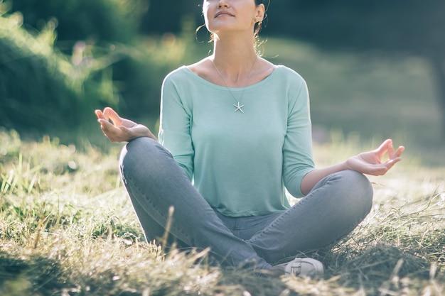 Młoda kobieta w pozycji lotosu na tle przyrody niewyraźne. zdjęcie z miejscem na kopię