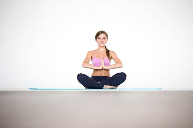 Młoda kobieta w pozycji lotosu. uprawianie jogi w pomieszczeniu.