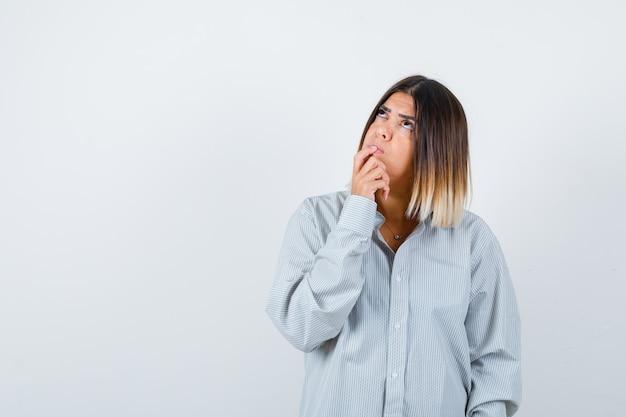 Młoda kobieta w przewymiarowanej koszuli stojąca w pozie myślenia i patrząca zamyślona, widok z przodu.