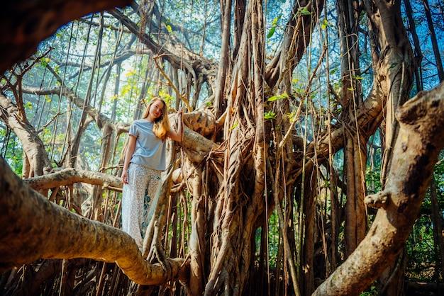 Młoda kobieta w przypadkowej odzieży pozuje na banyan drzewie