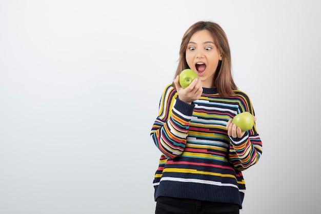Młoda kobieta w przypadkowy strój je zielone jabłko na białym tle.