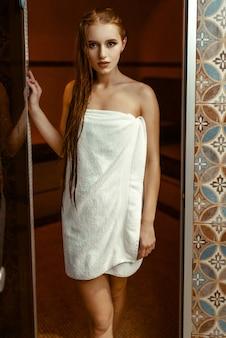 Młoda kobieta w ręcznik w saunie fińskiej.