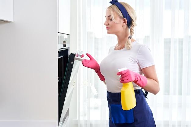 Młoda kobieta w rękawiczkach do czyszczenia piekarnika w kuchni. koncepcja usługi czyszczenia