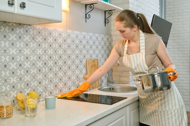 Młoda kobieta w rękawiczkach fartuch, sprzątanie kuchni po gotowaniu