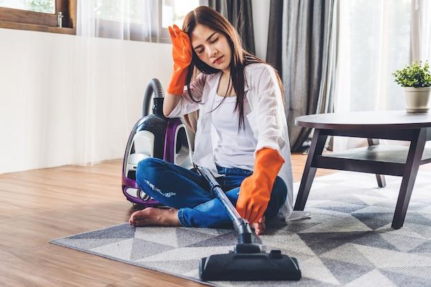 Młoda kobieta w rękawiczkach ochronnych czyści do domu z odkurzaczem w żywym pokoju w domu