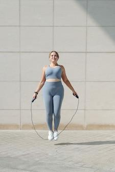 Młoda kobieta w rozmiarze plus size skacze ze skakanką na zewnątrz, aby rozgrzać się przed treningiem