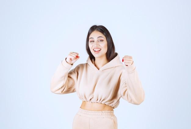 Młoda kobieta w różowej bluzie czuje się silna i potężna