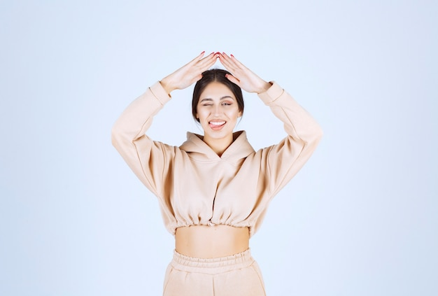 Młoda kobieta w różowej bluzie z kapturem, co dach nad głową