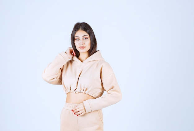 Młoda kobieta w różowej bluzie z kapturem, dając neutralne pozy