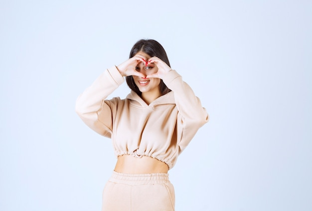 Młoda kobieta w różowej bluzie z kapturem daje urocze i serdeczne pozy