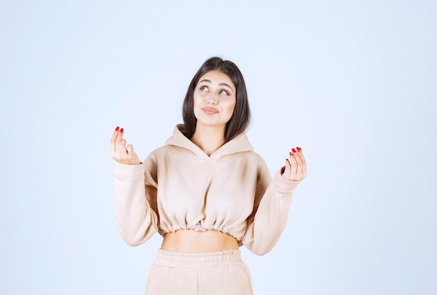 Młoda kobieta w różowej bluzie z kapturem, łącząc ręce i modląc się