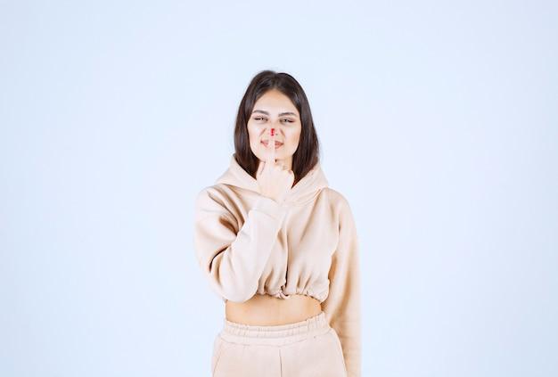 Młoda kobieta w różowej bluzie z kapturem myśli i burzy mózgów