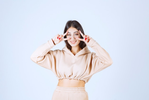 Młoda kobieta w różowej bluzie z kapturem, patrząc na jej palce