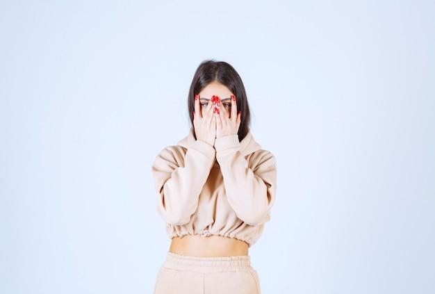 Młoda Kobieta W Różowej Bluzie Z Kapturem, Patrząc Na Jej Palce Darmowe Zdjęcia