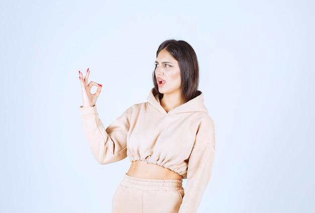 Młoda kobieta w różowej bluzie z kapturem pokazuje dobrą ręką znak