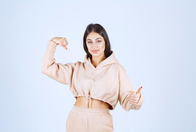 Młoda kobieta w różowej bluzie z kapturem pokazuje jej mięśnie